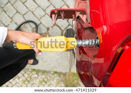 Close-up Of Businesswoman's Hand Refueling Her Car