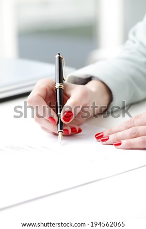 Close-up of businesswoman's hand, while fill the form. Small business.
