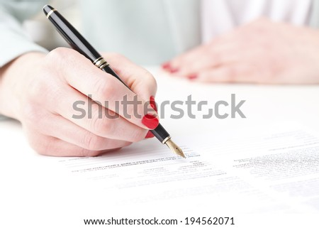 Close-up of businesswoman's hand, while fill the form. Small business. - stock photo