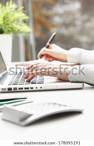 Close-up of businesswoman's hands doing paperwork.