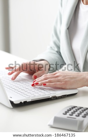 Close-up of businesswoman's hands while working on laptop and analyzing data. Small business. - stock photo