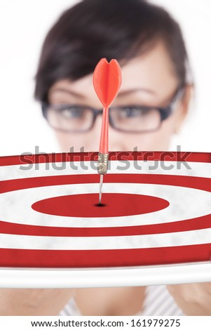 Close up of businesswoman showing a dartboard - stock photo