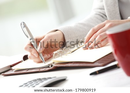 Close-up of businesswoman sitting in office and making list.