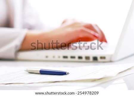 Close-up of businesswoman  typing documents on keyboard of laptop. selective view - stock photo