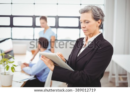 Close-up of businesswoman using digital tablet while colleagues in background at office