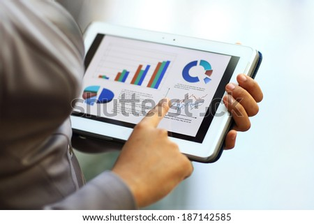 Close-up of businesswoman using tablet computer to work with financial data - stock photo