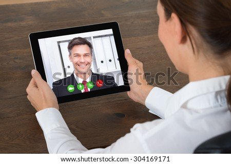 Close-up Of Businesswoman Videochatting With Senior Colleague On Digital Tablet At Desk - stock photo