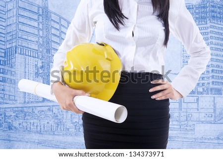 Close-up of businesswoman with safety helmet on blueprint background
