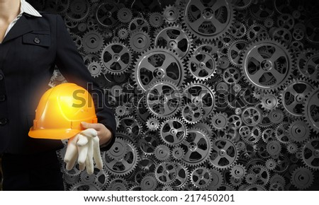 Close up of businesswoman with yellow hardhat in hand - stock photo