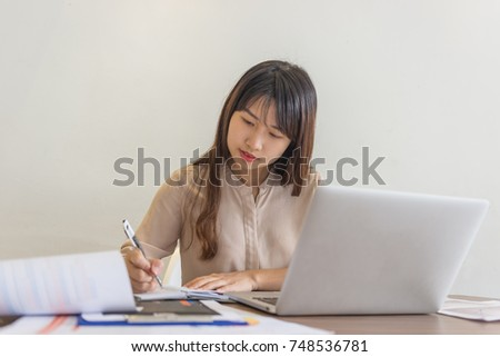 Close-up of businesswoman writing notes in office
