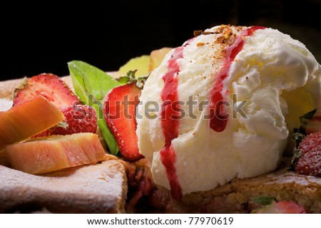 Close-up of cake with strawberries and ice-cream on black background - stock photo