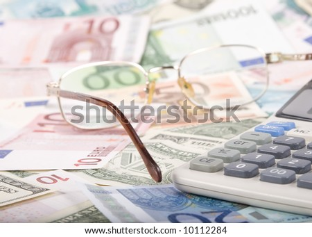Close-up of calculator and glasses on background from various banknotes.