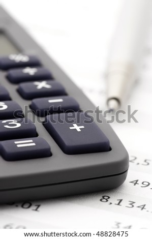 Close-up of calculator and pen on paper table with numbers.