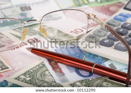 Close up of calculator, glasses and pen on background from various banknotes.