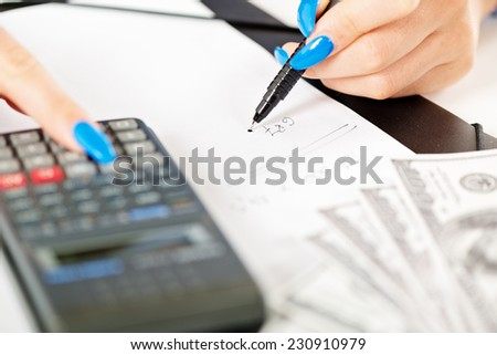 Close-up of calculator on white paper and women hands with long painted nails on the fingers that hold a pencil and write down the numbers on the paper next to a dollar bill. - stock photo