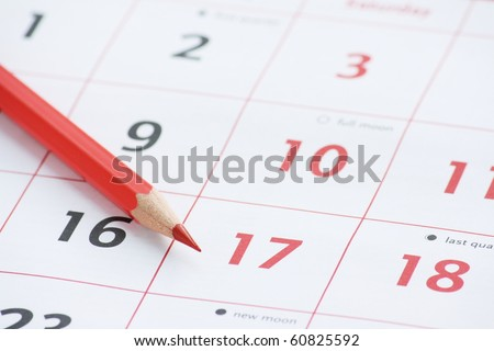 Close up of calendar dates and a red pencil for your time management and appointment reminders. - stock photo