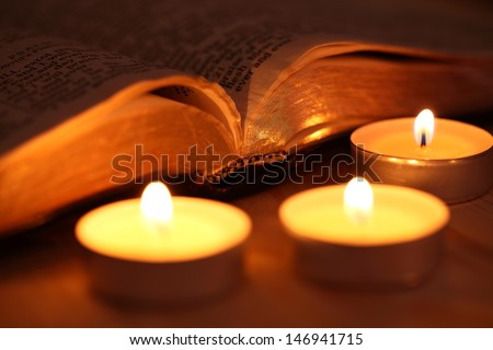Close-up of candles and open Bible - stock photo