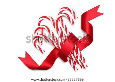 Close up of candy canes tied with ribbon on white background - stock photo
