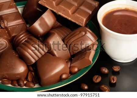 Close-up of cappuccino in porcelain cup, lots of various chocolates and coffee grains near by - stock photo