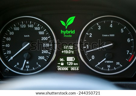 Close up of car dashboard with green hybrid mode icon on. - stock photo
