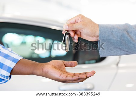 close up of car dealer handing over new car key to customer at showroom - stock photo