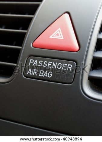close up of car interior showing the passenger airbag switch and hazard button. - stock photo