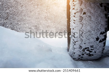 Close up of car tire on the snowy road with copy space - stock photo