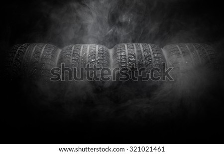 Close-up of car tires with smoke over black background - stock photo