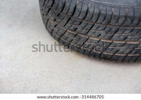 Close up of car tyre tread on the road on a bright day