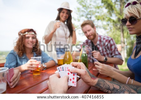 Close up of cards in hands of hipster male playing cards