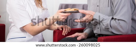 Close-up of care assistant giving pensioner cookies - stock photo