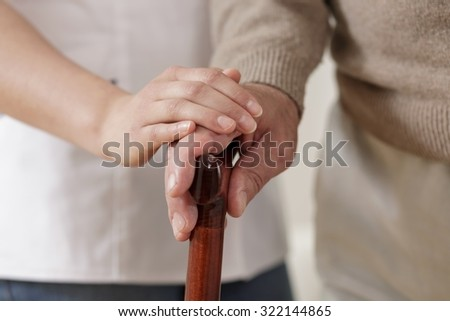Close up of carer holding old man hand