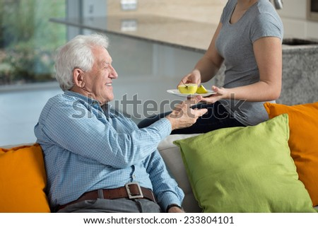 Close-up of caring daughter giving ill grandpa apple - stock photo
