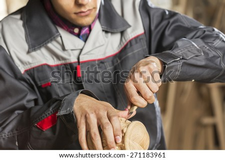 Close up of carpenter's hands working with cutter in his studio - stock photo