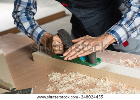 Close up of carpenter's hands working with the jointer - stock photo