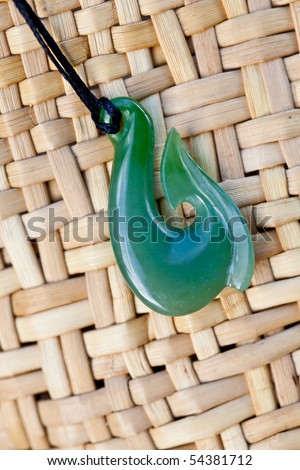 close up of carved maori nephrite jade / greenstone pendant on woven kite bag - stock photo