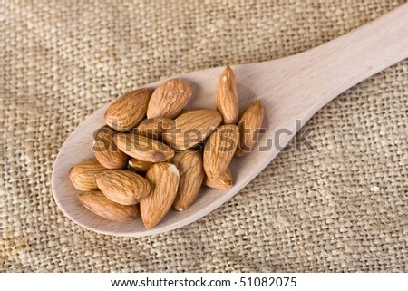 close up of cashew nuts on wooden spoon with hessian background