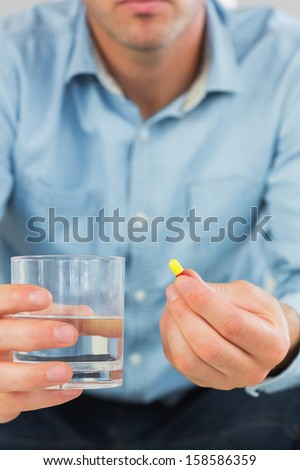 Close up of casual man holding a pill and glass of water in bright living room