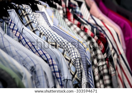Close up of casual shirts in different colors an patterns on rack - stock photo