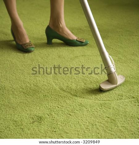 Close-up of Caucasian female feet with vacuum extension against green retro carpet. - stock photo