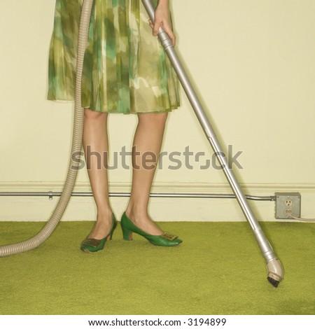 Close-up of Caucasian female legs with vacuum extension against green retro carpet. - stock photo