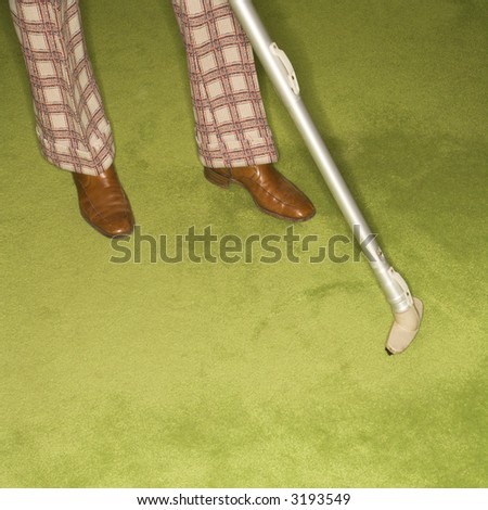 Close-up of Caucasian male feet with vacuum extension against green retro carpet. - stock photo