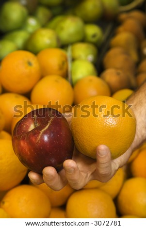 Close-up of Caucasian male hand holding apple and orange.