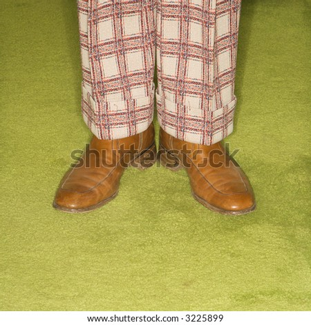 Close-up of Caucasian male legs in plaid pants standing on green retro carpet. - stock photo