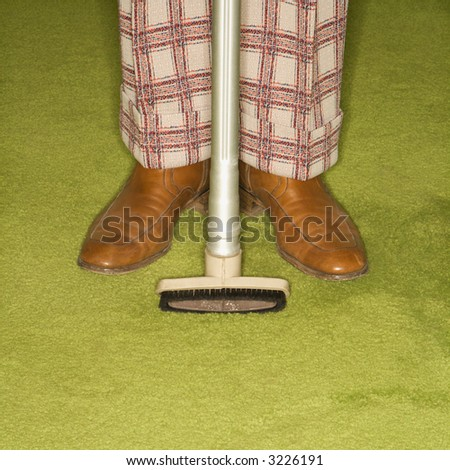 Close-up of Caucasian male legs in plaid pants with vacuum extension standing on green retro carpet. - stock photo