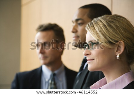 Close-up of Caucasian mid-adult businesswoman with two businessmen in background. Horizontal format. - stock photo