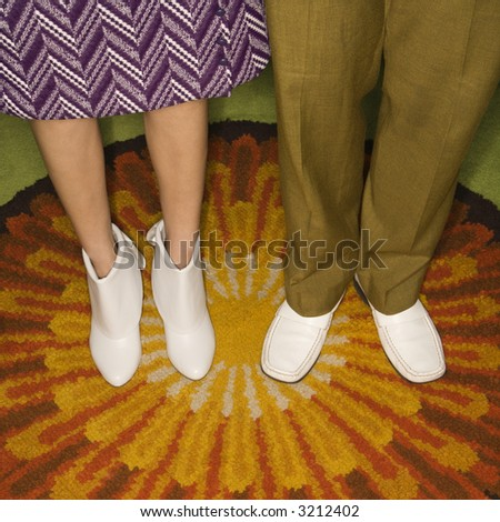 Close-up of Caucasian mid-adult male and female legs in vintage clothing against sunburst rug. - stock photo