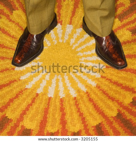 Close-up of Caucasian mid-adult male feet in vintage boots against sunburst rug. - stock photo