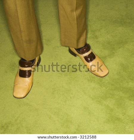 Close-up of Caucasian mid-adult male feet in vintage shoes against green rug. - stock photo