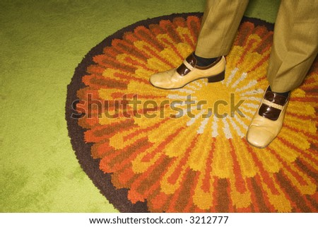 Close-up of Caucasian mid-adult male feet in vintage shoes against sunburst rug. - stock photo